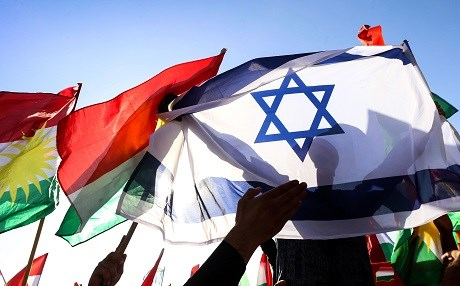 A man holds the Israeli flag as others raise the flag of the Kurdistan Region during a demonstration outside the UN Office in Erbil, the capital of the autonomous region, protesting against the escalating crisis with Baghdad. Photo: AFP/ Safin Hamed