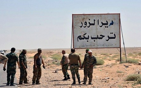 "This file photo released Sept. 3, 2017, by the Syrian official news agency SANA, shows Syrian troops and pro-government gunmen standing next to a sign in Arabic which reads, ""Deir el-Zour welcomes you,"" in the eastern city of Deir el-Zour, Syria. Photo: SANA via AP, File"