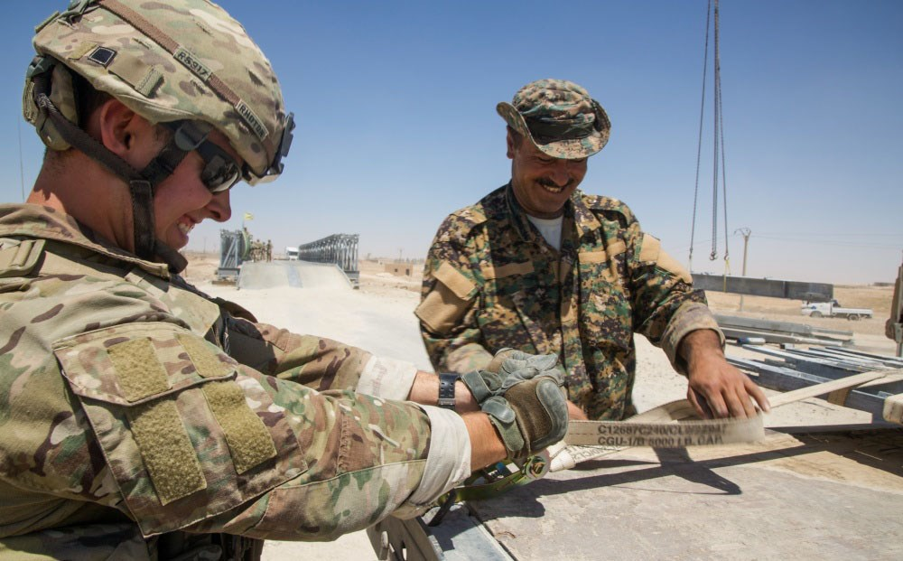 A US army engineer works with a member of the SDF to help maintain a bridge near Raqqa in July. Photo: Sgt. Mitchell Ryan/US Army