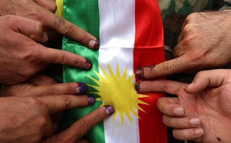 Members of a Kurdish Peshmerga battalion showing their ink-stained fingers in front of a Kurdish flag after voting in the Kurdish independence referendum in Erbil. File photo: AFP / Safin Hamed