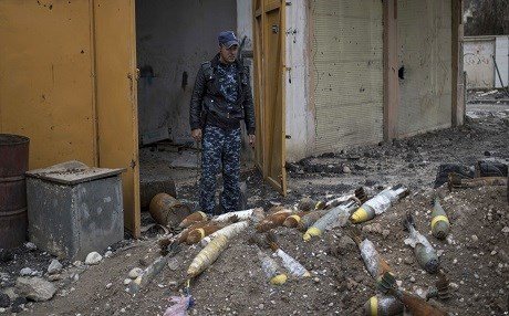 A member of Iraq's federal police stands in front of explosives in Mosul. Photo: AP