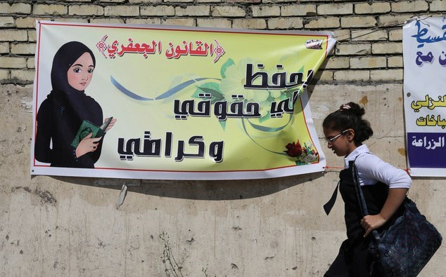 A schoolgirl passes a banner promoting the Jaafari Personal Status law in 2014. The banner states that the law