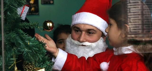 a man dressed as santa claus plays with a child during a christmas event at the - Who Celebrates Christmas