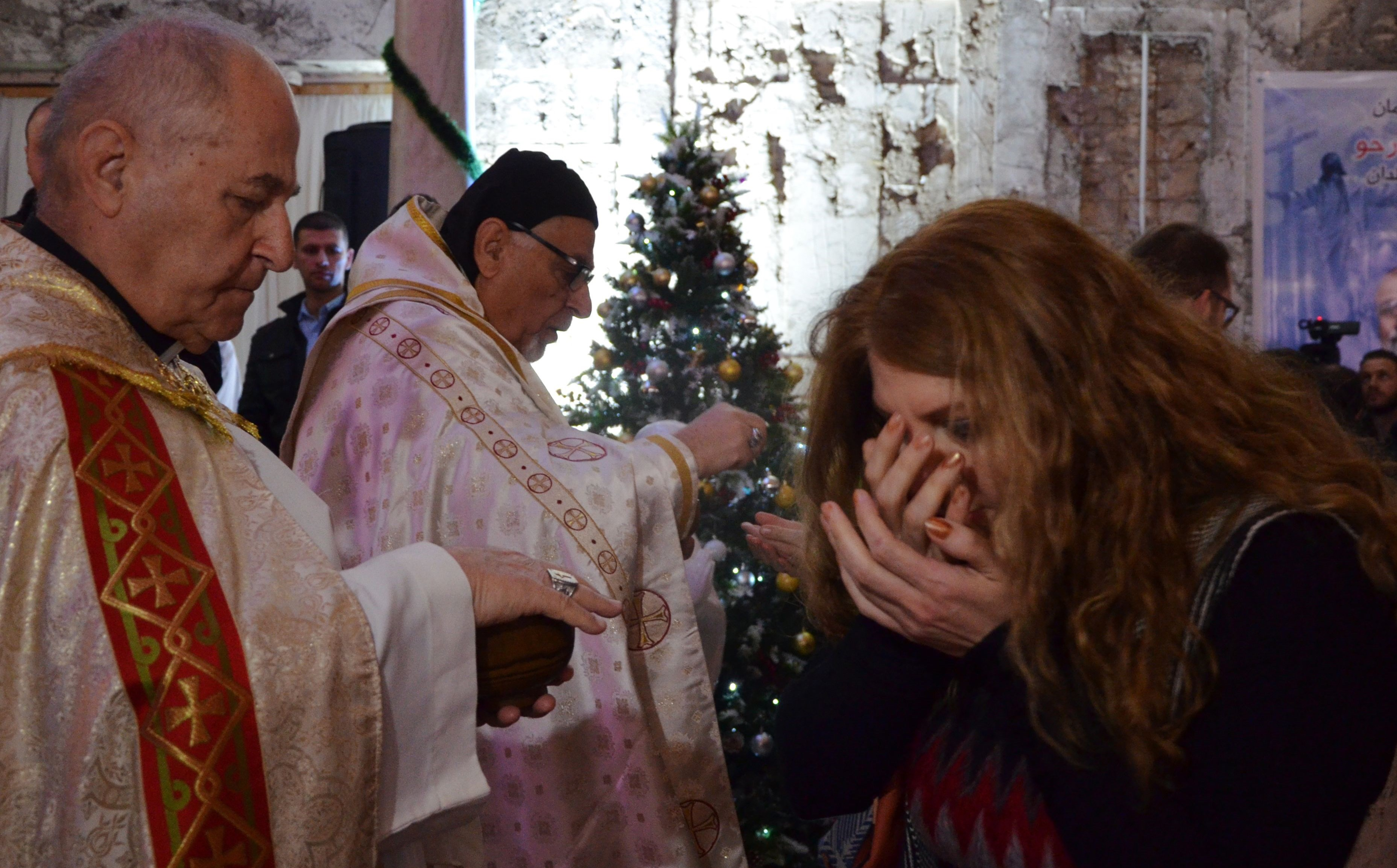 An Iraqi woman receives the Eucharist during Christmas mass at Saint Paul's church in Mosul. Photo: Ahmad Muwafaq/AFP