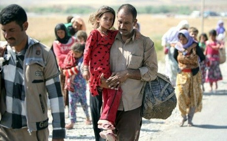 A Yezidi man carries his child as they flee ISIS on August 11, 2014. Photo: Ahmad al-Rubaye/AFP