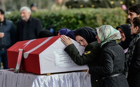 The wife (R) of a Turkish soldier killed in cross-border clashes with Kurdish People's Protection Units (YPG) forces in Afrin, reacts over his Turkish flag-draped coffin during a funeral ceremony in Istanbul on January 28, 2018. Photo:AFP/Yasin Akgul