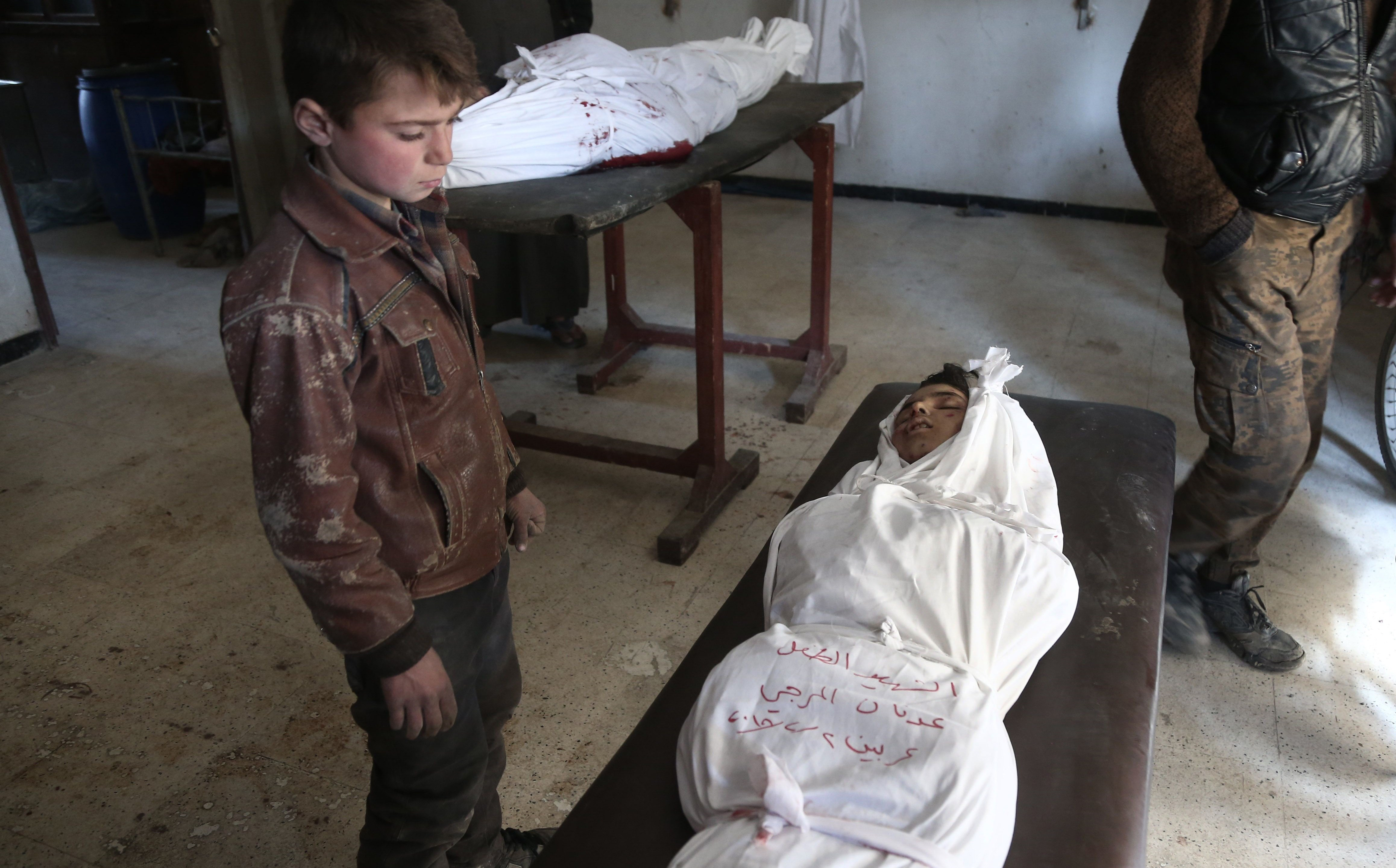 A Syrian child stands over the body of a child in a makeshift hospital following an airstrike on the rebel-held town of Arbin, in eastern Ghouta on Friday. Photo: Abdulmonam Eassa/AFP