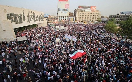 Iraqis demonstrators gathered in Tahrir Square wave their national flag and chant against corruption and poor services in Baghdad. Photo: AFP file photo