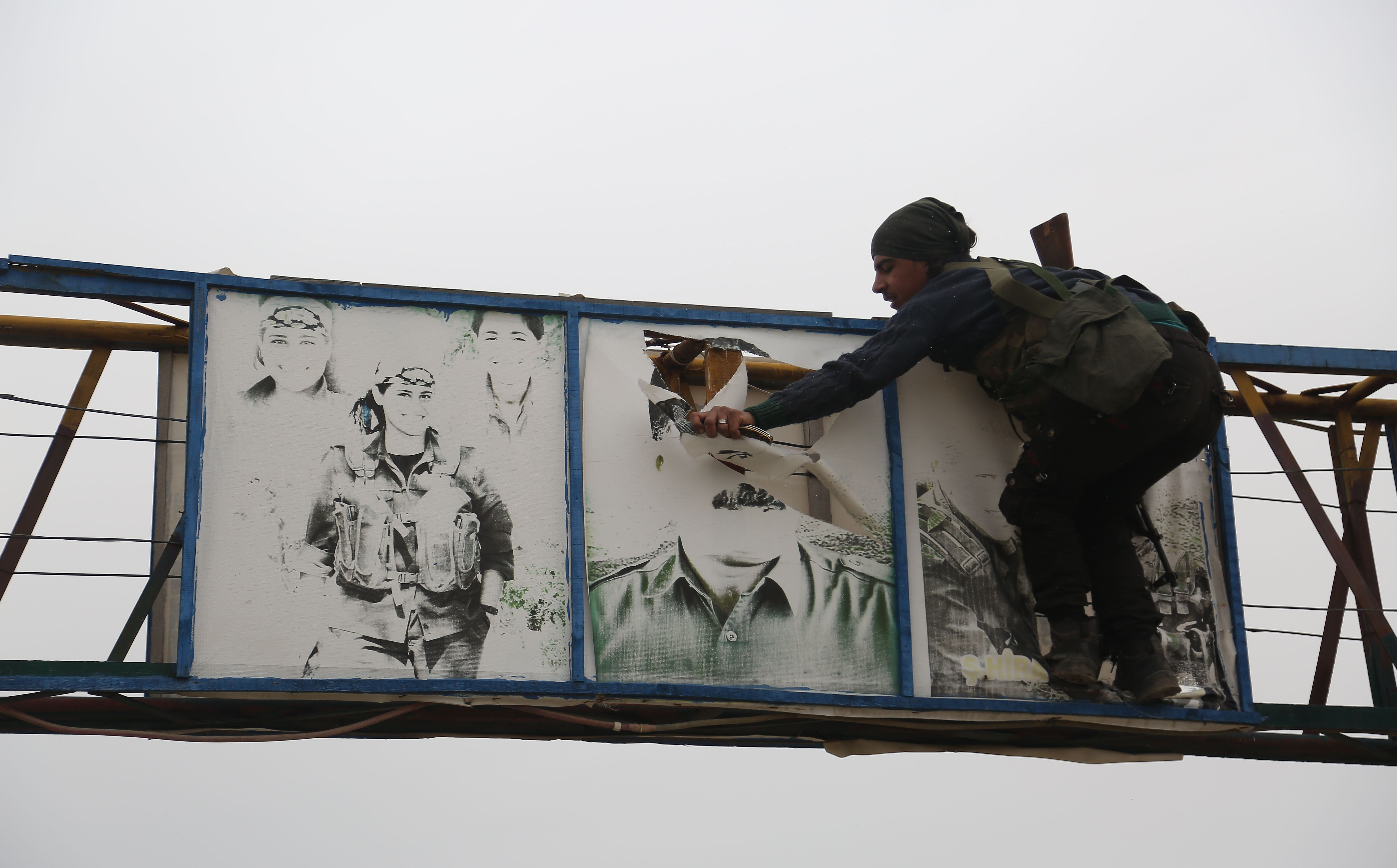 A Turkish-backed Syrian fighter tears down a picture of Abdullah Ocalan in the Hallubi area, north of Afrin, on Thursday. Photo: Nazeer al-Khatib/AFP
