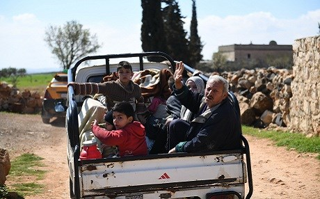 Civilans fleeing Afrin sit in the back of a pick up truck upon their arrival into government-controlled territory on Tuesday. Photo: George Ourfalian/AFP