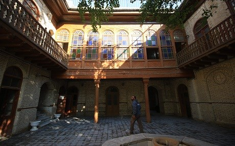 An Iraqi man walks in the courtyard of an old building with traditional