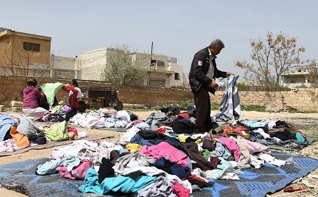 People displaced from Afrin sort through clothing donations in Tal Rifaat this week. Photo: George Ourfalian/AFP