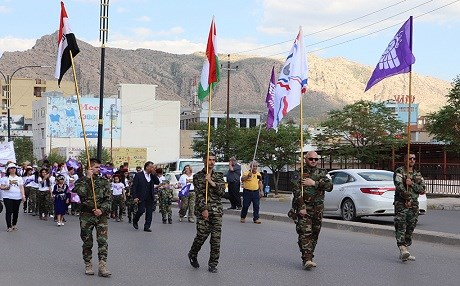 People carry the Iraq and Kurdistan's flags, as well as Assyrian ones during an Akitu parade on April 1, 2018. Photo: Vanessa Powell | Rudaw