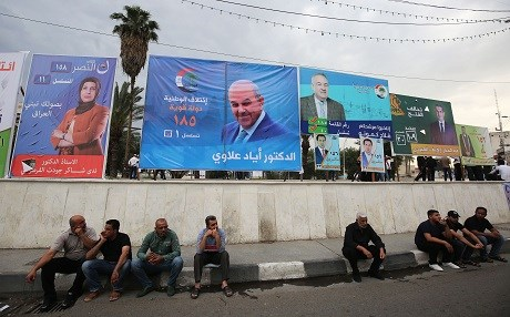 In Baghdad, Iraqis sit in front of campaign posters for candidates in the upcoming parliamentary elections. Photo: Ahmad al-Rubaye/AFP