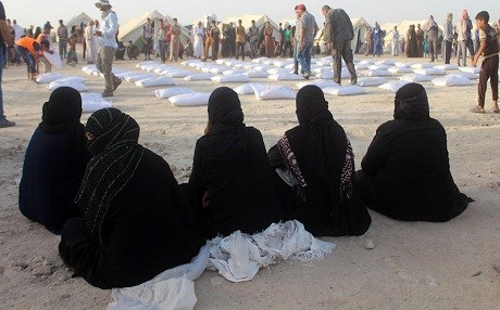 Iraqi women displaced from Ramadi, sit and wait to receive aid from the International Committee of the Red Cross at a makeshift camp where they are taking shelter in Habbaniyah, Anbar province, on June 23, 2016. File photo: Moadh al-Dulaimi | AFP