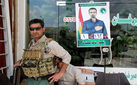 A private guard stands before a campaign poster for Rebwar Taha Mustafa, a PUK MP and candidate in oil-rich Kirkuk, on April 30, 2018. Photo: Sabah Arar | AFP