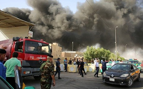 Fire crews work to extinguish the flames at an electoral commission warehouse in Baghdad on Sunday. Photo: Sabah Arar/AFP