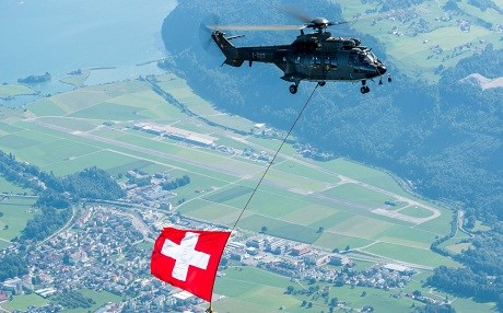 A helicopter flies over an air base in Switzerland while carrying the country's flag. Photo: Swiss Army