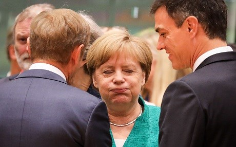 German Chancellor Angela Merkel (center) reacts as she speaks with European Council President Donald Tusk (left) and Spain's Prime Minister Pedro Sanchez during an European Union leaders' summit focused on migration, Brexit and eurozone reforms on June 28, 2018 at the Europa building in Brussels. Photo: Ludovic Marin | AFP