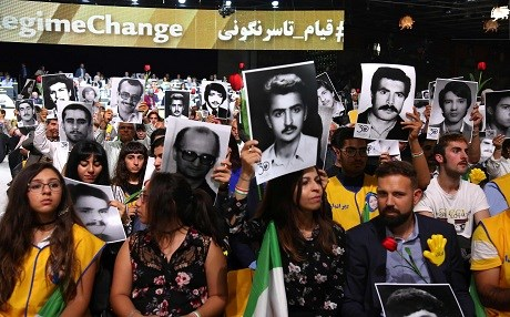 People hold up photos of family members killed by the Iranian regime during an MEK conference in Paris. Photo: Zakaria Abdelkafi/AFP