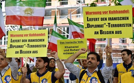 Activists of the National Council of Resistance of Iran (NCRI) hold placards reading 'Deliver the Iranian diplomat - terrorist to Belgium' during a demonstration calling for the extradition of a secret service officer to Belgium in front of the Federal Foreign Office in Berlin on July 11, 2018. Photo: Tobias Schwarz | AFP