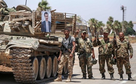 Syrian soldiers stand flashing the victory gesture next to a picture of Syrian President Bashar al-Assad hanging on a tank at the Nassib border crossing with Jordan in the southern province of Daraa on July 7, 2018. Photo: Youssef Karwashan | AFP