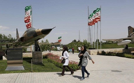 Iranians walk past a fighter jet at the Holy Defence Museum in Tehran. Photo: Atta Kenare/AFP