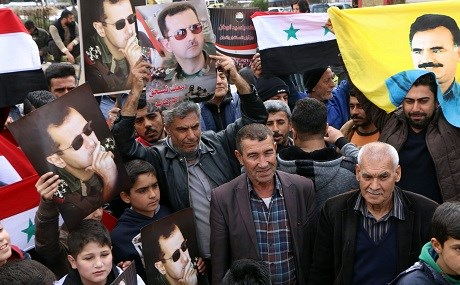 Afrin residents welcome arrival of Syrian regime forces with posters of President Bashar al-Assad and PKK founder Abdullah Ocalan, February 2018. File photo: Ahmad Shafie Bilal / AFP