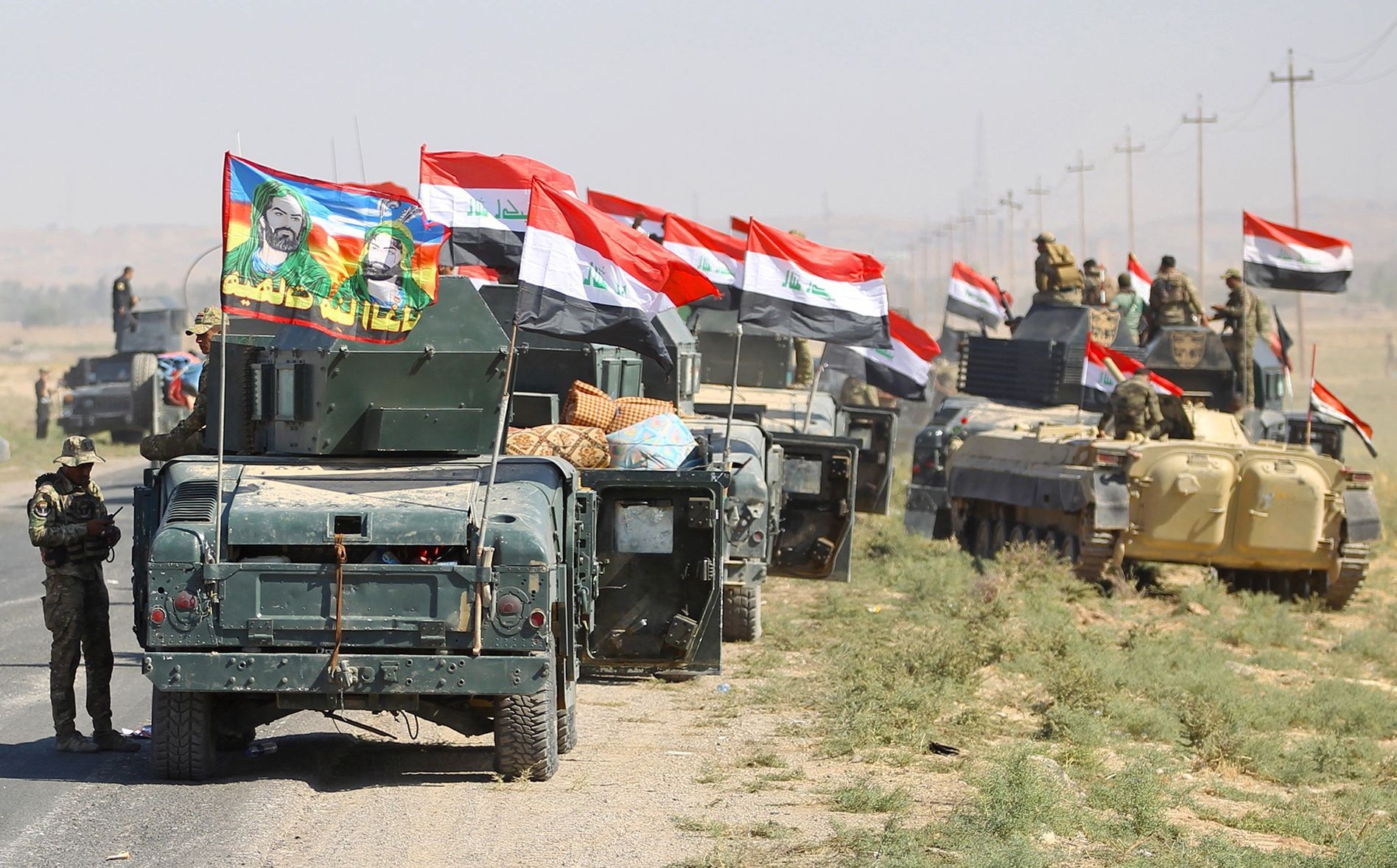 Iraqi troops with religious banners flying atop their vehicles advancing on Kirkuk, Oct. 2017. Photo AFP