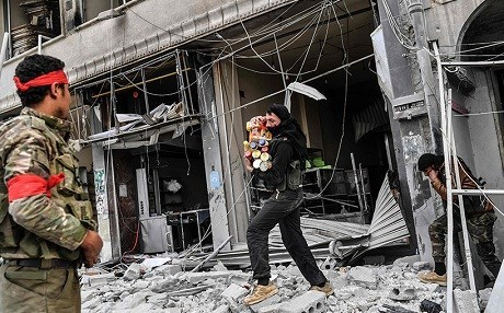 Syrian militiamen were pictured looting Kurdish businesses in Afrin after taking control of the city in March: File photo: AFP