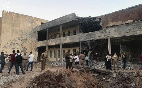 People gather at the headquarters of the PDKI, heavily damaged in a deadly Iranian missile strike on Saturday. Photo: Rudaw