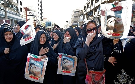 Iranian women hold images of one of the victims, Mohammad Taha Eghdami, 4, during a public funeral ceremony on Monday for those killed during an attack on a military parade in Ahvaz. Photo: Atta Kenare/AFP
