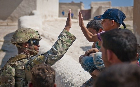 A US soldier high-fives a child while on patrol in Manbij. Photo: Staff Sgt. Timothy R. Koster/US Army