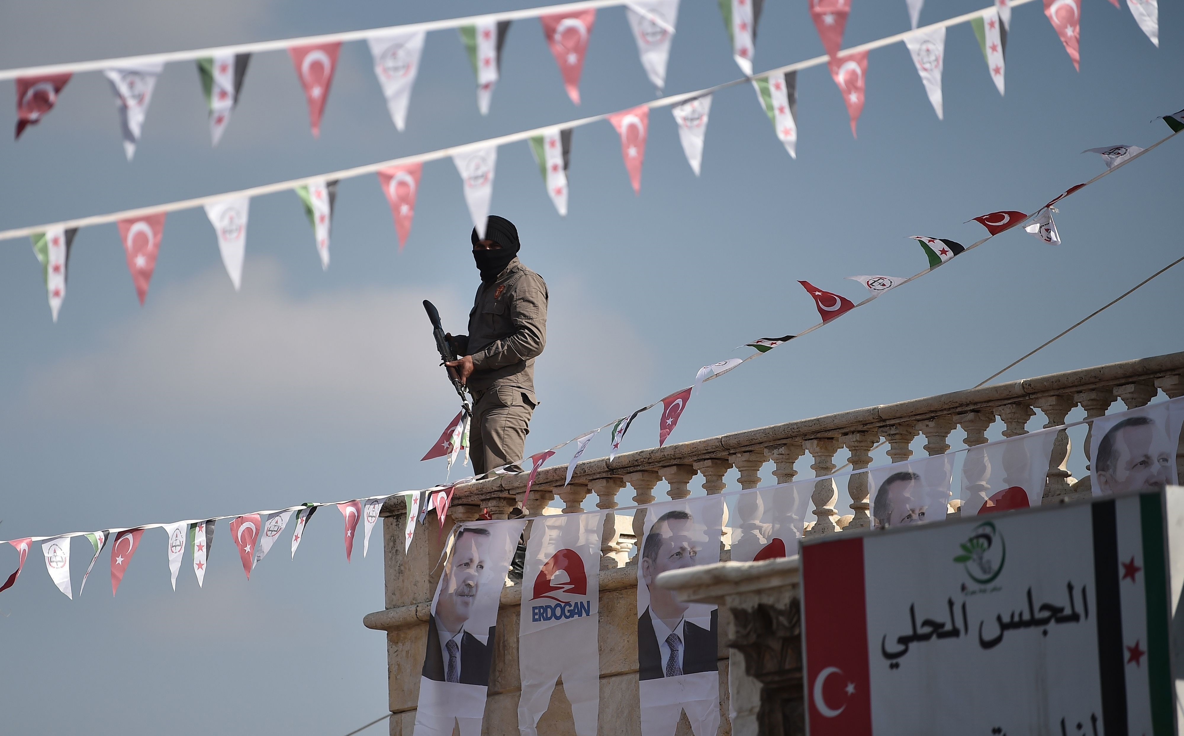 A Turkish-backed Syrian opposition fighter stands on a rooftop in Suran, Syria decorated with posters of Turkey President Recep Tayyip Erdogan. File photo: Ozan Kose / AFP