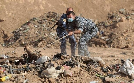Iraqi police try to pull a body from a mass grave they discovered south of Mosul in November 2016. File photo: Ahmad al-Rubaye | AFP