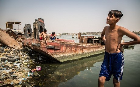Children swim in the trash-strewn Shat al-Arab river in Basra. Photo: Tom Peyre-Costa/NRC