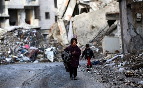 Syrian children walk past destruction in the city of Raqqa. File photo: AFP