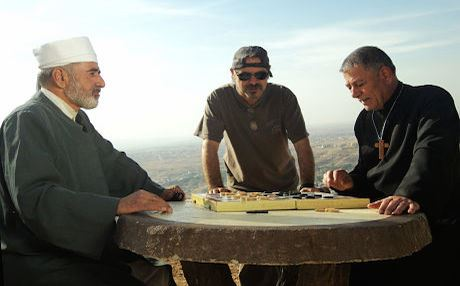 Kurdish-American filmmaker Jano Rosebiani (center) with actors Ghazi Ghefur (priest) and Ismail Salih (Mella Issa). Photo courtesy of Evini Films