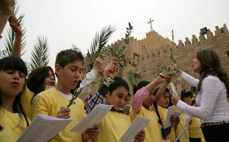 Iraqi Christian children hold olive branches as they read religious texts outside St. Joseph Church in Erbil, capital of the Kurdistan Region. Photo: AFP