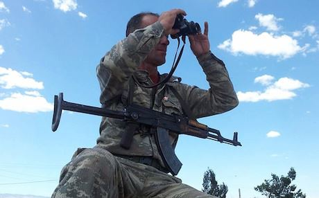 A YPG fighter scans the area with binoculars. Photo: Flickr
