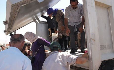 Refugees being helped off a truck arriving in Sharya. Photo by author.