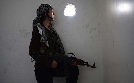 A woman member of the Kurdish Peoples Protection Units (YPG) takes position inside a ruined house in Aleppo amid clashes with Syrian regime forces. Photo: AFP