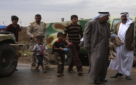 An Iraqi soldier escorts civilians as they leave anti-government protests in Hawija, April 22. Photo: AP