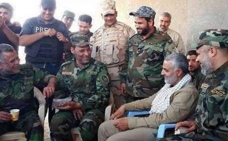 General Suleimani (seated in light uniform) chats with Hadi al-Ameri (seated left) and other unidentified soldiers.