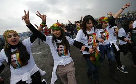 Supporters of the Kurdistan Workers Party (PKK) dance in T-shirts adorned with images of the groups imprisoned leader Abdullah Ocalan. Photo: Rudaw