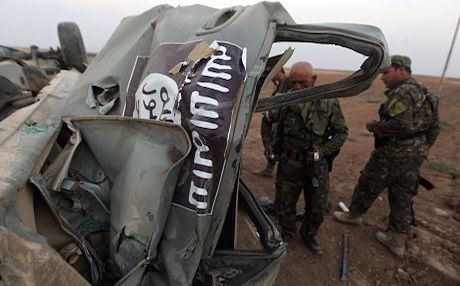 Kurdish Peshmerga fighters inspect an ISIS vehicle destroyed by a US airstrike. Photo: AFP
