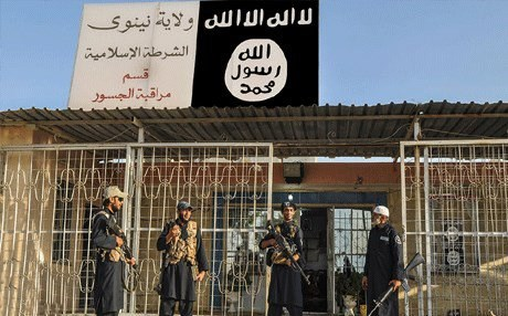 ISIS militants in front of a police station in Nineveh province, Iraq — AP.