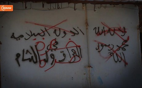 ISIS graffiti crossed out by Kurdish forces in Shingal